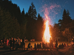 a group of young people stand and sit on benches watching a bonfire that reaches more than twenty feet in the air