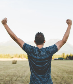 man from back with hands raised in victory looking at a harvested field