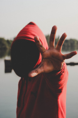 man in a red hoodie shading his face stretching his hand out to stop the camera