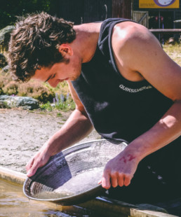 man in tank top looking down into the water as he pans for gold