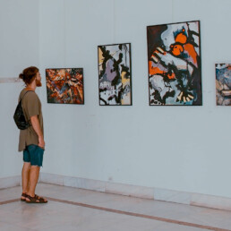 man looking at a line of artwork hanging on a gallery wall