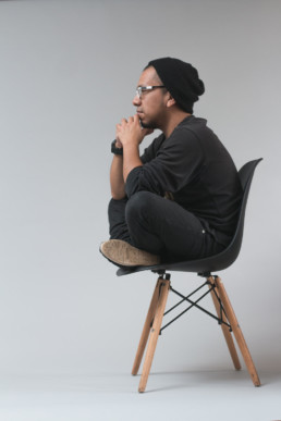 sitting cross-legged on a chair thinking deeply