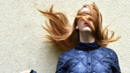 lady with hair swirling around head, covering eyes