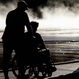 Silhouette of a man pushing someone in a wheelchair across a boardwalk ramp